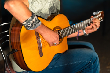Man playing yellowe an acoustic guitar closeup
