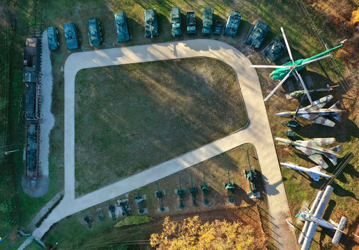 Aerial view of the base of military equipment. Ground with old tanks, helicopter, train
