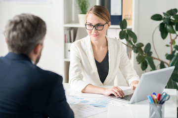 Content attractive female business consultant in glasses sitting at table in office and typing on laptop while working with client and explaining data to him