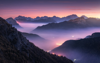 Fotobehang Aubergine Mountains in fog at beautiful night in autumn in Dolomites, Italy. Landscape with alpine mountain valley, low clouds, forest, purple sky with stars, city illumination at sunset. Aerial. Passo Giau