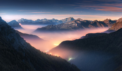 Poster Night blue Mountains in fog at beautiful night in autumn in Dolomites, Italy. Landscape with alpine mountain valley, low clouds, forest, colorful sky with stars, city illumination at dusk. Aerial. Passo Giau