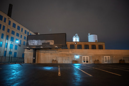 Scary industrial urban street city night scene with vintage factory warehouses and a decaying billboard over an empty parking lot with silos in the background