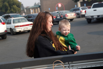 Sonya Butts, 28, whose home in Paradise was destroyed by the Camp Fire, holds her son, Landyn, 3, while shopping for new household items in Chico