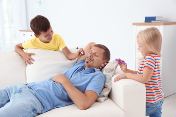 Little children painting their father's face while he sleeping on couch at home. April fool's day prank