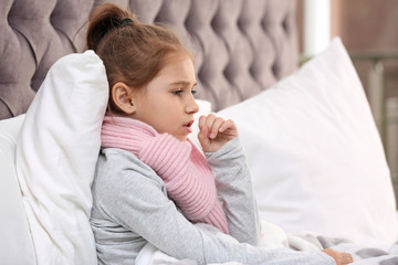 Little girl suffering from cough and cold in bed at home