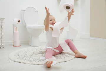 Cute little girl playing with toilet paper in bathroom
