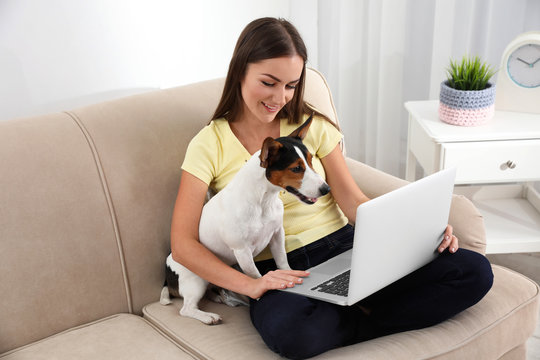 Beautiful woman with her dog working on laptop at home