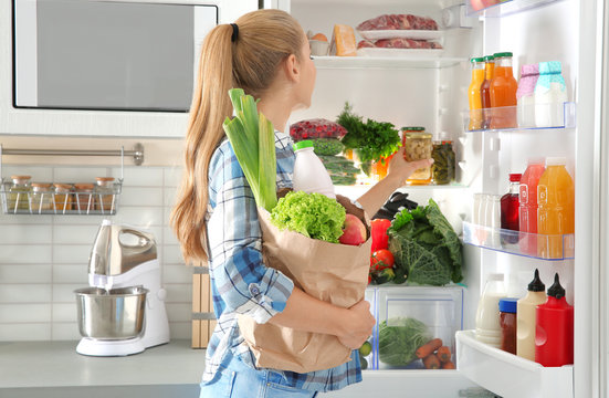 Woman putting products into refrigerator in kitchen