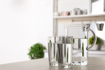 Glassware of fresh water on table indoors. Space for text