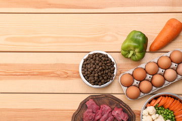 Flat lay composition with dry and natural dog food on wooden background. Space for text