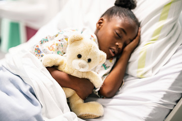Little girl sleeping in a hospital bed