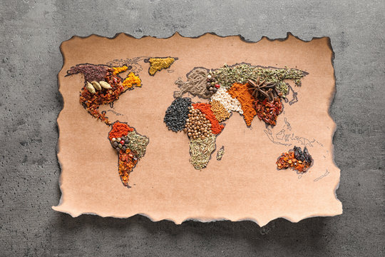 Paper with world map made of different aromatic spices on gray background, top view