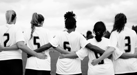 Female soccer players huddling and standing together