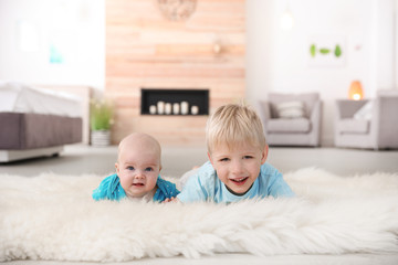 Cute boy with his little sister lying on fur rug at home