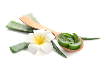 Wooden spoon with pieces of aloe vera and flower on white background
