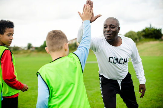 Football coach doing a high five with his student