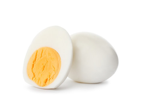 Sliced and whole hard boiled eggs on white background