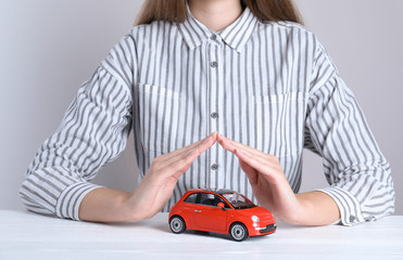 Insurance agent covering toy car on table, closeup