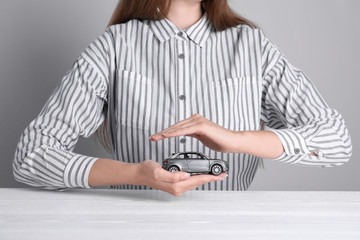 Insurance agent covering toy car at table, closeup