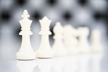 Set of white chess pieces on white background