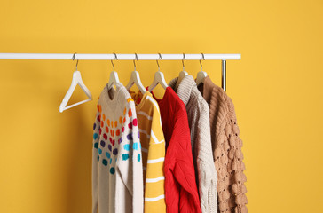 Fototapete - Collection of warm sweaters hanging on rack against color background