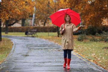 Woman with umbrella taking walk in autumn park on rainy day Fotobehang