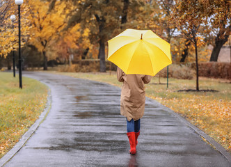 Woman with umbrella taking walk in autumn park on rainy day