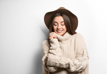 Beautiful young woman in warm sweater with hat on white background. Space for text