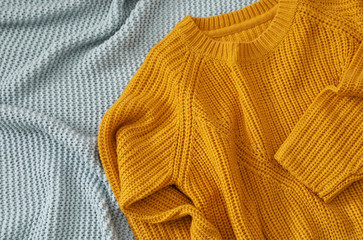 Fototapete - Cozy knitted sweater on blanket, above view. Space for text