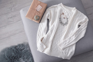 Fototapete - Cozy knitted sweater with jewelry and gift on pouf in living room, flat lay. Space for text