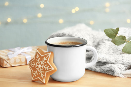 Composition with cup of hot winter drink and Christmas cookie on table. Cozy season