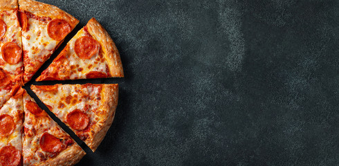 Stores photo Pizzeria Tasty pepperoni pizza and cooking ingredients tomatoes basil on black concrete background. Top view of hot pepperoni pizza. With copy space for text. Flat lay. Banner