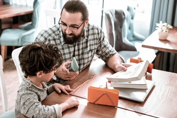 Private tutor. Bearded dark-haired private tutor teaching cute preschooler reading and writing