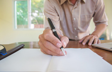 Businessman hand writing with document at home office.concept