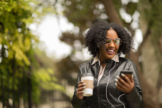 African American Woman texting and drinking coffee.