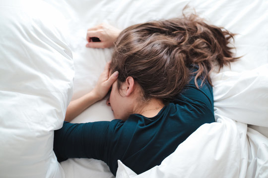 young woman in bed holding her head