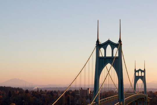 Portland's St. Johns Bridge at dawn with Mt St. Helens in the distance. With tall Gothic Cathedral Spires and graceful arches, it is the largest and most significant suspension bridge in Oregon.