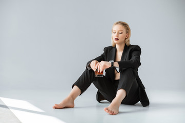 elegant young woman in black trendy suit holding glass of whiskey and sitting on grey