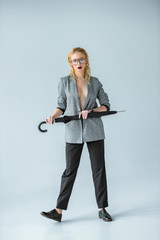 attractive young woman in trendy gray jacket posing with umbrella on grey