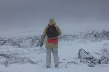 Winter trip to the mountains in cloudy windy weather in poor visibility