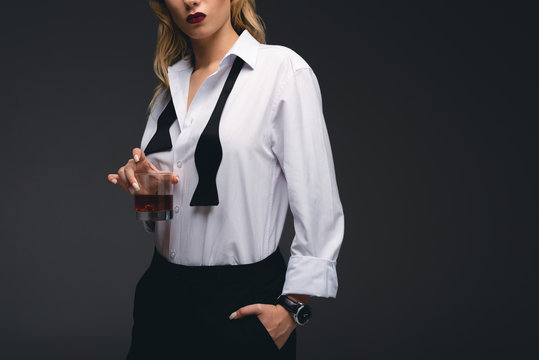 cropped view of elegant girl in formal wear holding glass of whiskey, isolated on dark grey