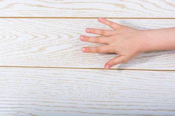 Hand making a gesture on wooden background