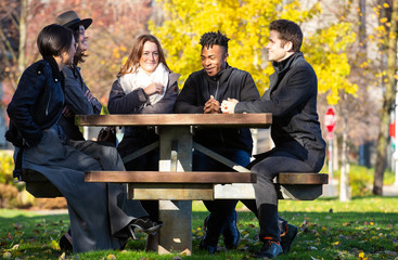 Group of people sitting outside at table during the Fall