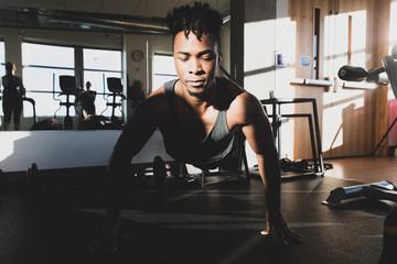 Healthy man doing pushups during a workout in a gym