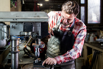 Portrait of blacksmith in leather apron drills workpiece