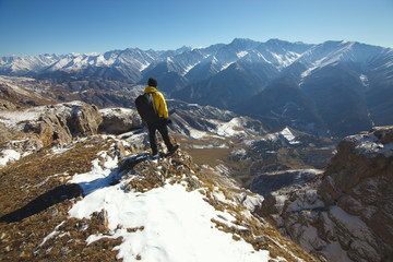 A traveler at the top of the mountain observes the surrounding landscape.