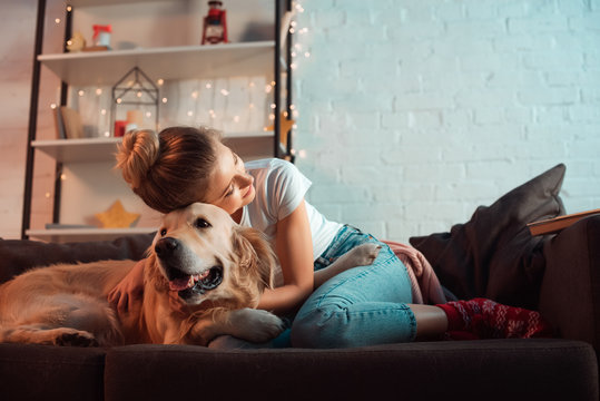 young blonde woman on couch hugging golden retriever dog at christmas time