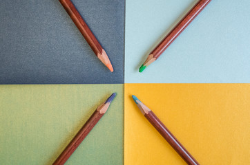 Colored pastel pencils are on colored paper.