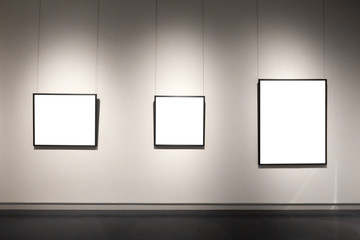 white picture frames on black wall in long corridor of a gallery