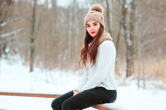 winter close up portrait of beautiful young woman in knitted hat and sweater walking in snowy park or forest, spending weekend outdoor